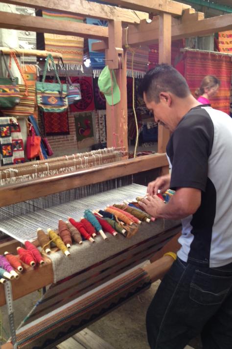 Don Porfirio, con sus hilos de muchos colores, nos demuestra cómo usa el telar.